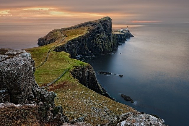 A rocky island in the middle of a body of water with Neist Point in the background