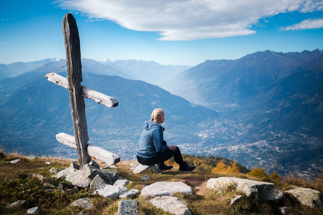 A man sitting on a rock in front of a mountain