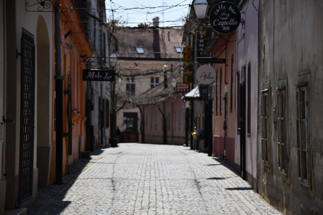 A narrow city street with buildings in the background