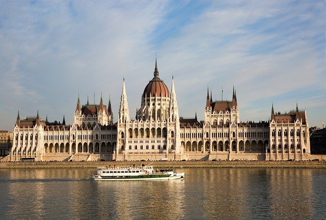 A castle with water in front of Hungarian Parliament Building
